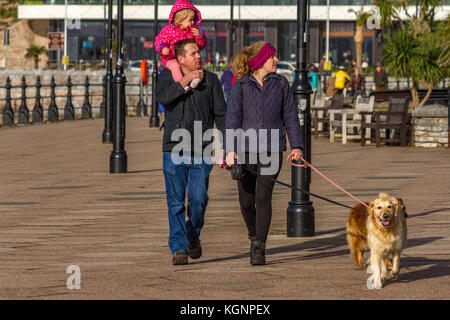 A family including a couple, with their young child on the man's shoulders, and their pet dog, walking along Torquay - Stock Photo