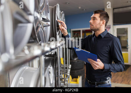 auto business owner and wheel rims at car service - Stock Photo