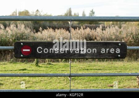 Close up of conservation area sign on galvanised metal gate in RSPB Fen Drayton Lakes, Cambridgeshire - Stock Photo