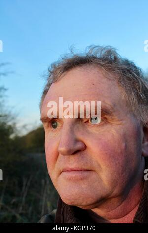 Close up face of 60 year old white man looking into evening sun at wildfowl on a lake - Stock Photo