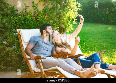 Young couple taking selfies - Stock Photo
