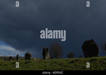 Stones at Averbury Stone Circle, beneath an approaching storm - Stock Photo