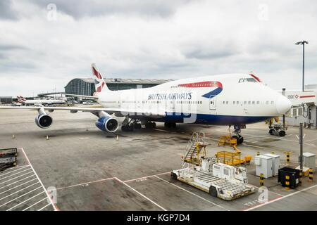 British Airways Boeing 747 airliner parks at a gate at Heathrow Airport Terminal 5 - Stock Photo