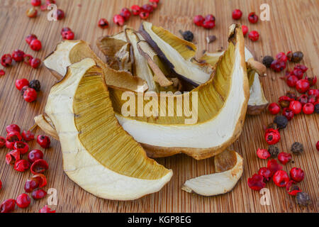 Pile of first class dried bolete mushrooms with red pepper grains on bamboo dark wooden background - Stock Photo