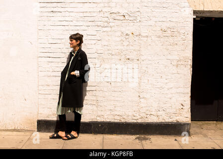 Hipster woman dressed in urban minimal style with long black jacket, striped dress, black trousers and sandals. - Stock Photo