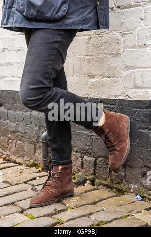 Model legs wearing tight black skinny trousers and brown ankle boots. Black and white brick wall as a background. - Stock Photo