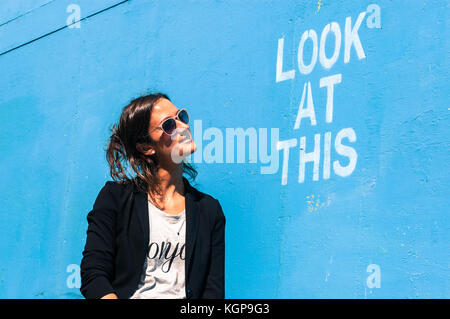 Hipster model wearing sunglasses posing next to a blue wall with the words 'Look at this' written on it - Stock Photo