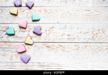 Pink, violet, yellow and green heart cookies on a white wooden background with copy space - Stock Photo