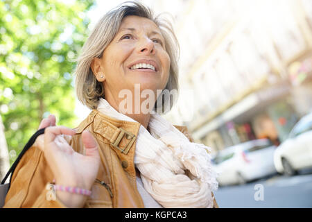 Portrait of senior woman in town on shopping day - Stock Photo