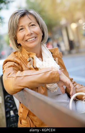 Senior woman on shopping day relaxing on bench - Stock Photo
