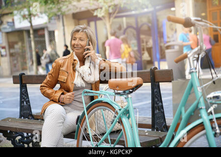 Senior woman in town with bike, talking on phone - Stock Photo