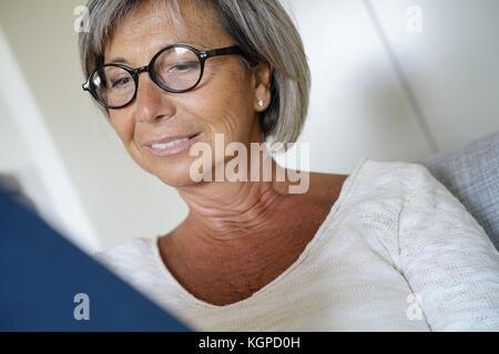 Senior woman with eyeglasses reading book in sofa - Stock Photo