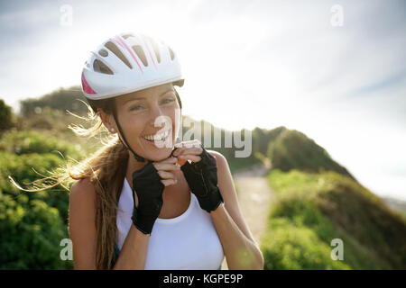 Portrait of smiling woman on bike ride putting helmet on - Stock Photo