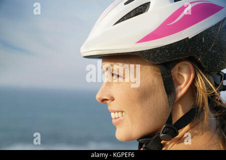 Profile view of woman on bike ride wearing protection helmet - Stock Photo