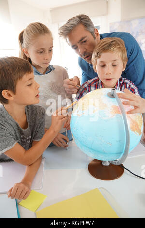 Teacher with kids in geography class looking at globe - Stock Photo
