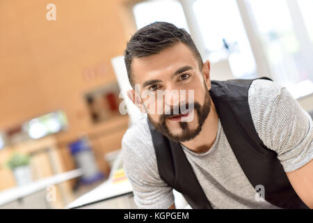 Portrait of cheerful trendy bearded guy in office - Stock Photo