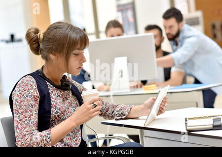 Trendy young woman in office working on tablet - Stock Photo