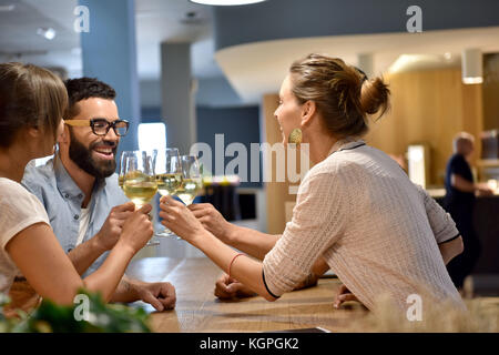 Friends in bar cheering with wine glasses - Stock Photo
