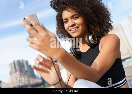 Fitness girl using smartphone and headset on jogging day - Stock Photo