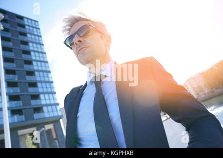 Mature businessman standing in front of building - Stock Photo