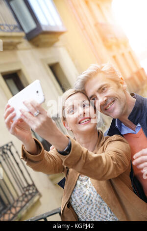 Couple taking selfie picture with smartphone in European city - Stock Photo