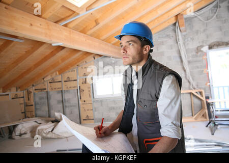 Construction manager on site reading blueprint - Stock Photo