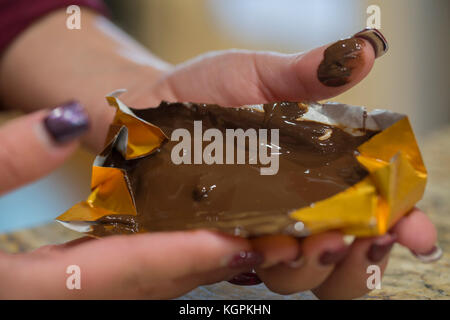 Young woman unwrapping a melted chocolate bar - Stock Photo