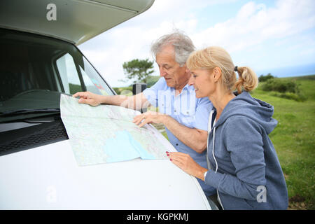 Senior people reading road map by camper - Stock Photo