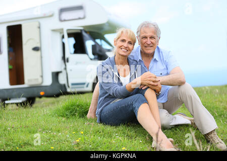 Happy senior couple sitting in grass, camper in background - Stock Photo