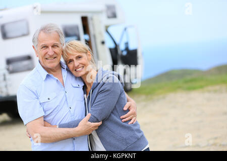 Cheerful senior couple standing by camper on road stop - Stock Photo