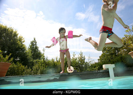 Kids jumping in swimming-pool - Stock Photo