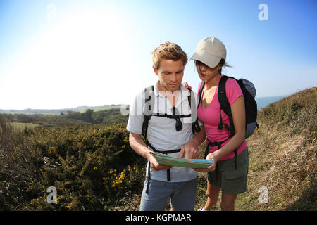 Hikers in country path looking at map - Stock Photo