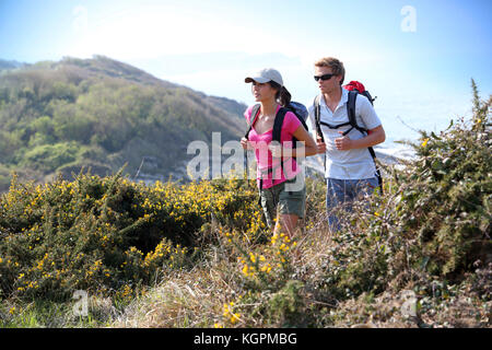 Couple of hikers in country field by the ocean - Stock Photo