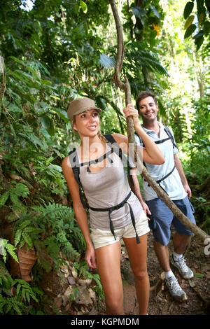 Couple on a trekking day in tropical forest - Stock Photo