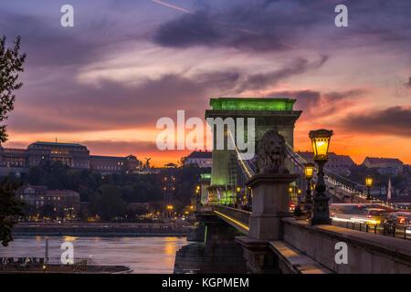 Budapest, Hungary - Beautiful dramatic golden sunset at Szechenyi Chain Bridge in green lights with Buda Castle - Stock Photo