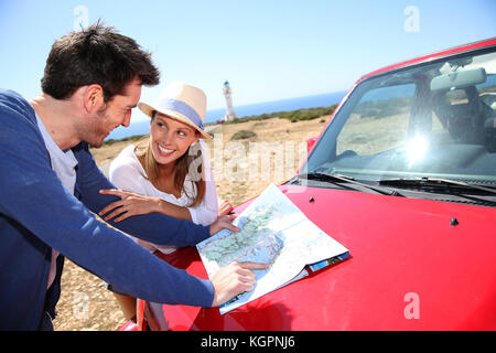 Couple looking at road map on red car hood - Stock Photo