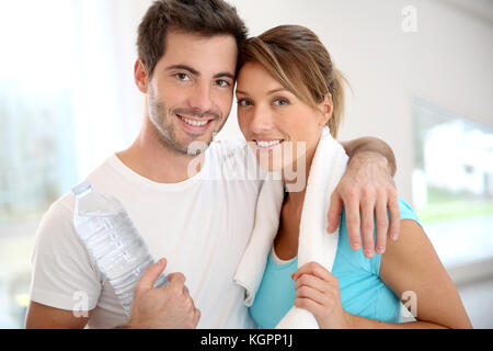 Portrait of smiling couple in fitness gym - Stock Photo