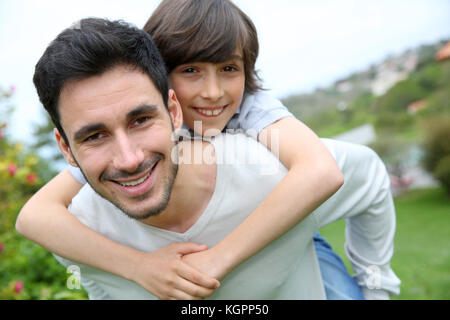 Father giving piggyback ride to his son - Stock Photo