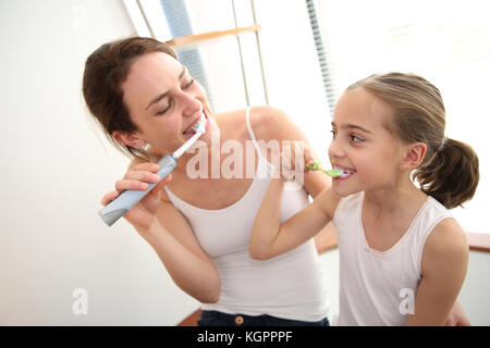 Mother teaching little girl how to brush her teeth - Stock Photo