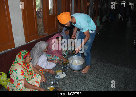 Sikh volunteers peeling Garlic and preparing food at the free community dining room. The Golden Temple. Amritsar. - Stock Photo