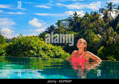 Woman on summer beach holiday relaxing in luxury spa hotel in infinity swimming pool with tropical jungle view. - Stock Photo