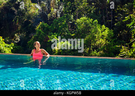 Beautiful tanned woman on summer beach holiday relaxing in luxury spa hotel in infinity swimming pool with tropical - Stock Photo