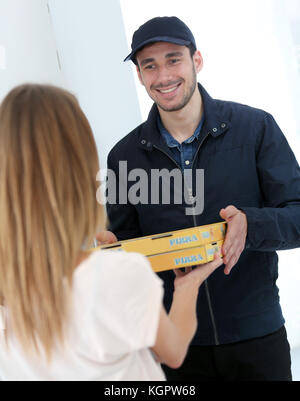 Smiling young man delivering pizza to customer - Stock Photo