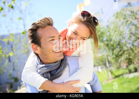 Man giving piggyback ride to woman in park - Stock Photo