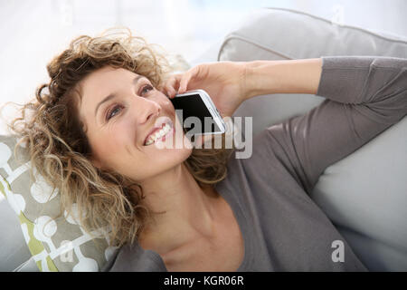 Woman talking on smartphone laid in sofa - Stock Photo