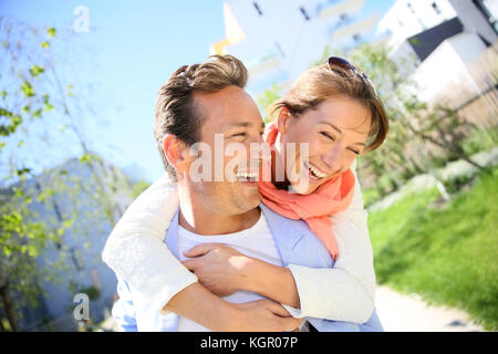Man giving piggyback ride to woman in town - Stock Photo