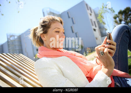 Woman relaxing in park and using smartphone - Stock Photo