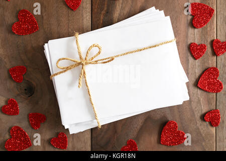 A stack of love letters in blank white envelopes tied with twine string bow is sitting on a rustic cherry wood plank - Stock Photo