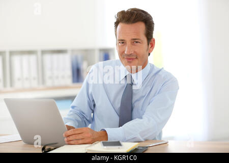 Handsome businessman in office working on laptop - Stock Photo