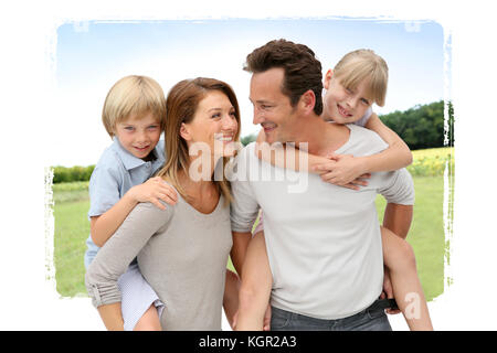 Parents giving piggyback ride to kids in countryside - Stock Photo
